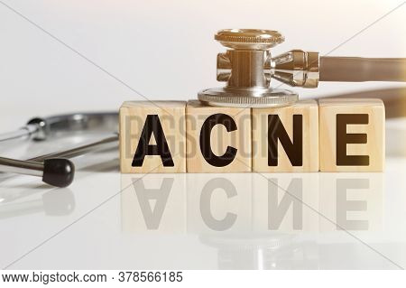 Acne The Word On Wooden Cubes, Cubes Stand On A Reflective White Surface, On Cubes - A Stethoscope.