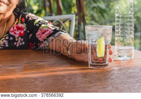 Senior Woman Holding Fresh Glass Of Water With Lime Detox Drink.