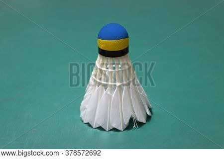 Used Shuttlecock And On Head Painted With Ukraine Flag Put Vertical On Green Floor Of Badminton Cour