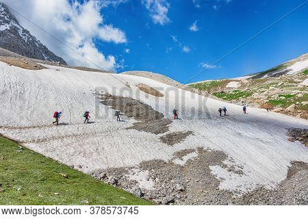 Idyllic Summer Landscape With Hiking Trail In Snow Mountains With Trekkers.