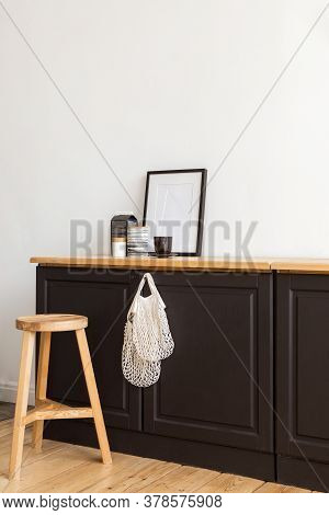 Modern Cupboard With Cotton Bags And Various Decorations Placed Near Wooden Stool Against White Wall