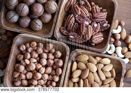 Different Nuts In Small Wooden Bowl On Dark Table. Row Of Bowls With Nuts, Top View. Peeled Nuts. He