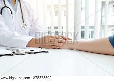 The Female Doctor Uses A Friendly Hand To Hold The Patient's Hand To Give Confidence And Show Care A