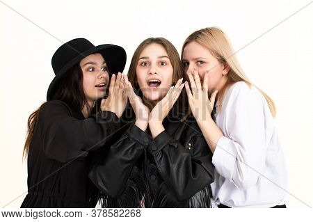 Three Young Beautiful Girls Are Discussing The News And One Is Very Surprised. Photo On A White Back