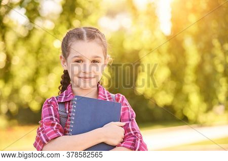 Young Schoolgirl With Backpack. Lifestyle Going To Classroom. Outdoor Autumn Park. Children Learn Sm