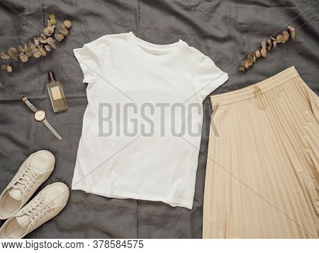 Fashionable Female Look With White Empty T-shirt, Cream Pleated Skirt And White Sneakers. Top View O