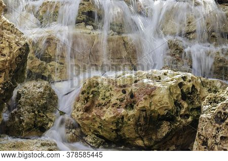 Slow Motion Of Water Jets Of Artificial Waterfalls On Natural Picturesque Textured Stones