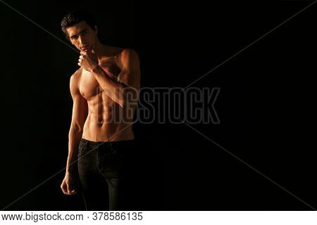 Strong Athletic Handsome Young Man With Naked Torso, Showing His Six Abs On Dark Black Background.