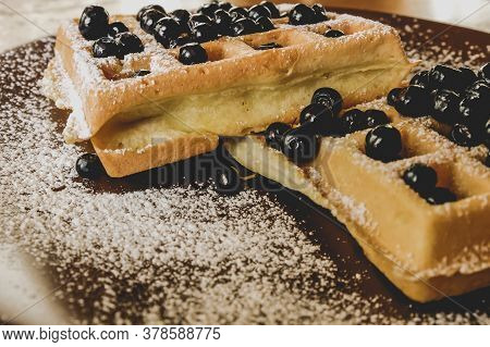 Belgian Waffles With Berries On A Plate With Powdered Sugar.