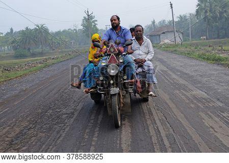 KUMROKHALI, INDIA - FEBRUARY 26, 2020: Indian tricycle motor rickshaw carrying passenger, Kumrokhali, West Bengal