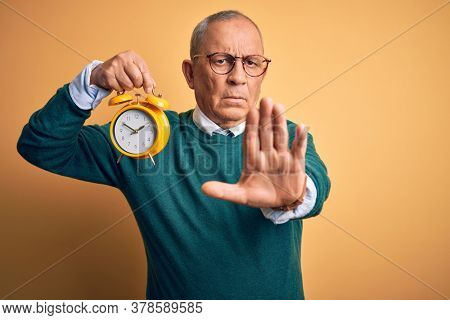Senior handsome man holding alarm clock standing over isolated yellow background with open hand doing stop sign with serious and confident expression, defense gesture
