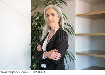 Pretty Gray-haired Businesswoman Standing With Folded Hands. Portrait Of Confident Young Pretty Fema