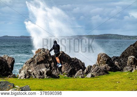 Man Standing At A Blowhole With Water Fountains At The Beautiful Coast Next To Carrickabraghy Castle