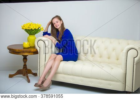 Beautiful Little Girl With Long Silky Hair, Sits On The Couch With A Bouquet Of Yellow Tulips. The C