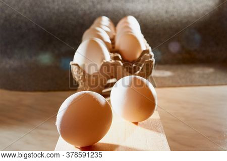 White Chicken Eggs In Cardboard On Wooden Surface With Interesting Light. The Concept Of Taking Pict
