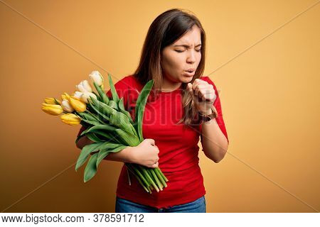 Young blonde woman holding romantic bouquet of tulips flowers over yellow background feeling unwell and coughing as symptom for cold or bronchitis. Health care concept.