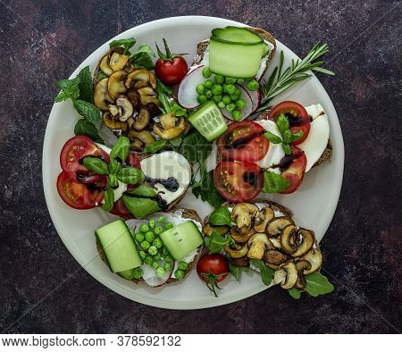 Plate With Vegetarian Sandwich Toasts With Different Toppings, Top View. Flat Lay Of Rye Bread Crost