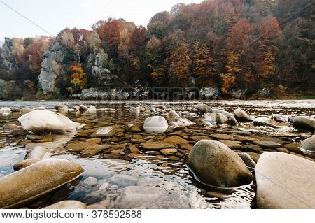 Clear River With Rocks Leads Towards Mountains. Lit By Sunset. Mountain Fast Flowing River Stream Of