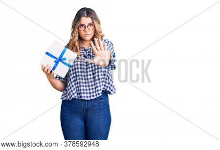 Young caucasian woman holding gift with open hand doing stop sign with serious and confident expression, defense gesture