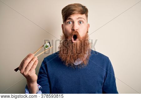 Redhead Irish man with beard eating green maki sushi using chopsticks over yellow background scared in shock with a surprise face, afraid and excited with fear expression