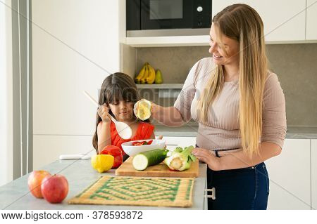 Mom And Daughter Cooking Vegs For Dinner At Kitchen Table. Girl And Her Mother Dressing Salad In Bow