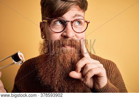 Redhead Irish man with beard eating salmon maki sushi using chopsticks over yellow background serious face thinking about question, very confused idea