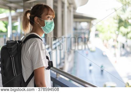 Asian Woman With Surgical Face Mask Feel Tired Standing On Skywalk After Travel By Skytrain, Carryin