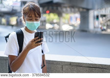 Asian Woman With Surgical Face Mask, Carrying Backpack,  Traveling To The City Use Smartphone Nearby