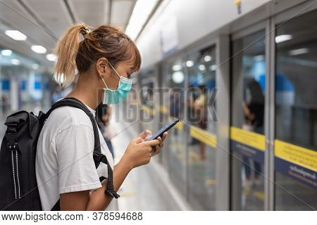 Asian Woman With Surgical Face Mask Feel Tired Use Smartphone Standing Waiting For Subway, Skytrain,
