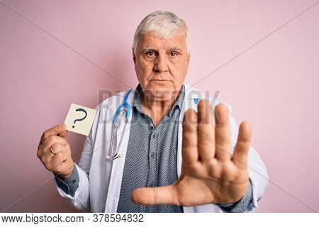 Senior handsome hoary doctor man wearing stethoscope holding reminder with question mark with open hand doing stop sign with serious and confident expression, defense gesture