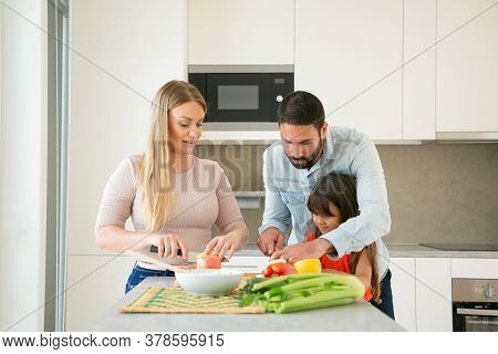 Mom And Dad Teaching Kid To Cook. Young Couple And Their Girl Cutting Fresh Fruit And Vegs For Salad