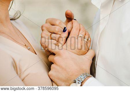 Cropped Photo Young Married Couple Holds Hands With Rings, Husband And Wife Outdoors. Rear View Of C