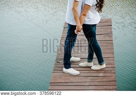Cropped Photo Young Lovers Married Couple, Husband And Wife, Held Of Hands On A Wooden Bridge Near L