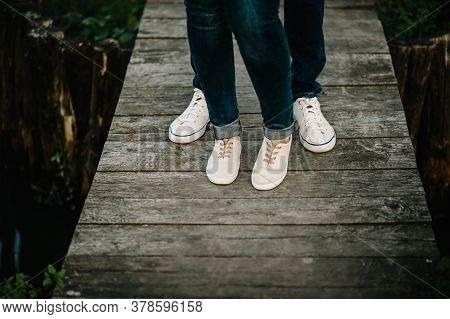 Cropped Photo Young Legs In Sneakers, Married Couple, Husband And Wife On A Wooden Bridge Near Lake.
