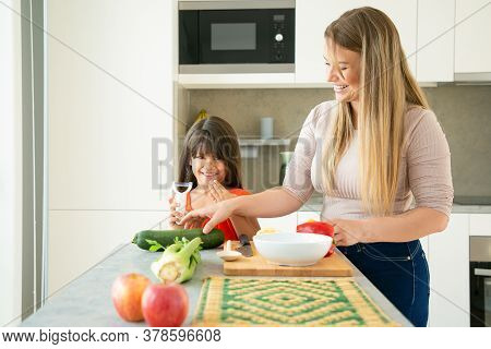 Cheerful Mom And Daughter Having Fun While Cooking Vegetables For Dinner. Girl And Her Mother Peelin
