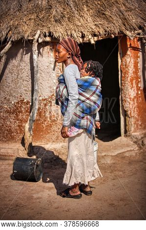 african woman carry her child, standing in front of her house in a village in Botswana