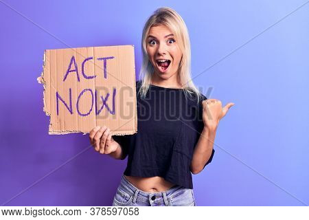 Young beautiful blonde woman asking for social reaction holding banner with act now message pointing thumb up to the side smiling happy with open mouth