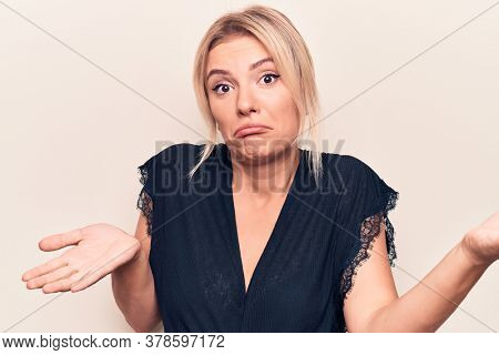 Young beautiful blonde woman wearing casual t-shirt standing over isolated white background clueless and confused expression with arms and hands raised. Doubt concept.