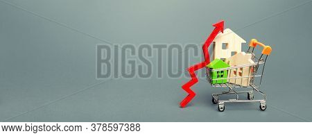 Wooden Houses In A Shopping Cart And Red Arrow Up. Real Estate Price Growth Concept. High Demand For