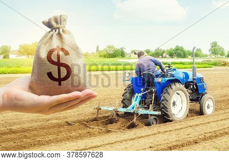 A Hand Holds Out A Dollar Money Bag On A Background Of Farmer On A Tractor Making Mounds Rows On A F