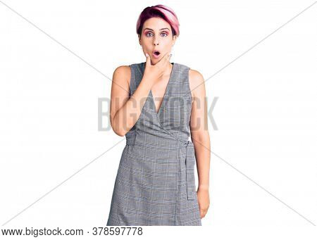 Young beautiful woman with pink hair wearing casual clothes looking fascinated with disbelief, surprise and amazed expression with hands on chin