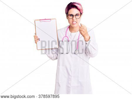 Young beautiful woman with pink hair wearing doctor stethoscope holding clipboard with medical report annoyed and frustrated shouting with anger, yelling crazy with anger and hand raised