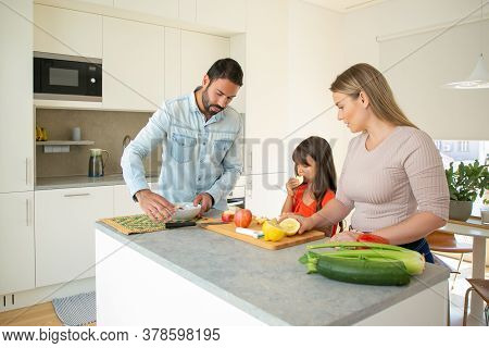 Happy Family Cooking Dinner Together. Young Couple And Kid Preparing Fresh Vegs For Salad At Kitchen