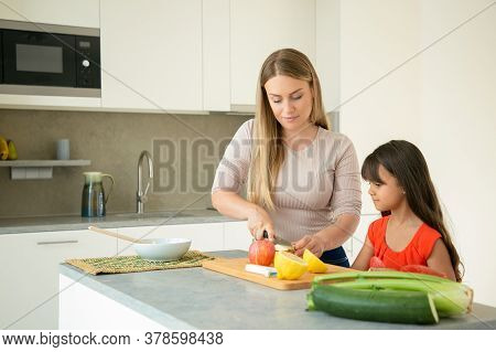 Mom Teaching Daughter To Cook. Girl And Her Mother Cooking Together, Cutting Fresh Fruits And Vegs O