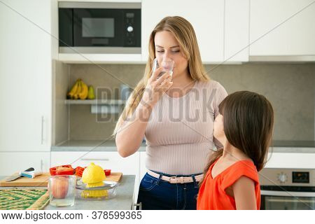 Mom And Daughter Drinking Water While Squeezing Lemon Juice, Cooking Salad Together In Kitchen. Fami