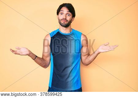 Handsome hispanic man wearing sportswear clueless and confused expression with arms and hands raised. doubt concept.