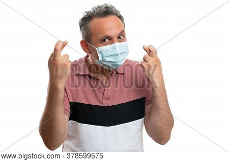 Cheerful Man Wearing Medical Disposable Mask And Showing Fingers Crossed As Good Luck Concept To Sto