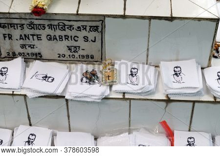 KUMROKHALI, INDIA - FEBRUARY 28, 2020: Religious objects are waiting for a blessing on the grave of Croatian missionaries, Jesuit father Ante Gabric in Kumrokhali, West Bengal, India