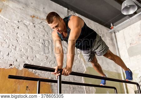 fitness, sport, bodybuilding and people concept - young man doing push-ups or high plank on parallel bars in gym