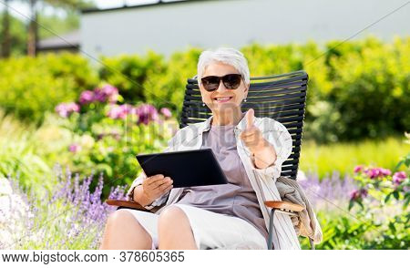technology, old age and people concept - happy smiling senior woman with tablet pc computer resting at summer garden and showing thumbs up